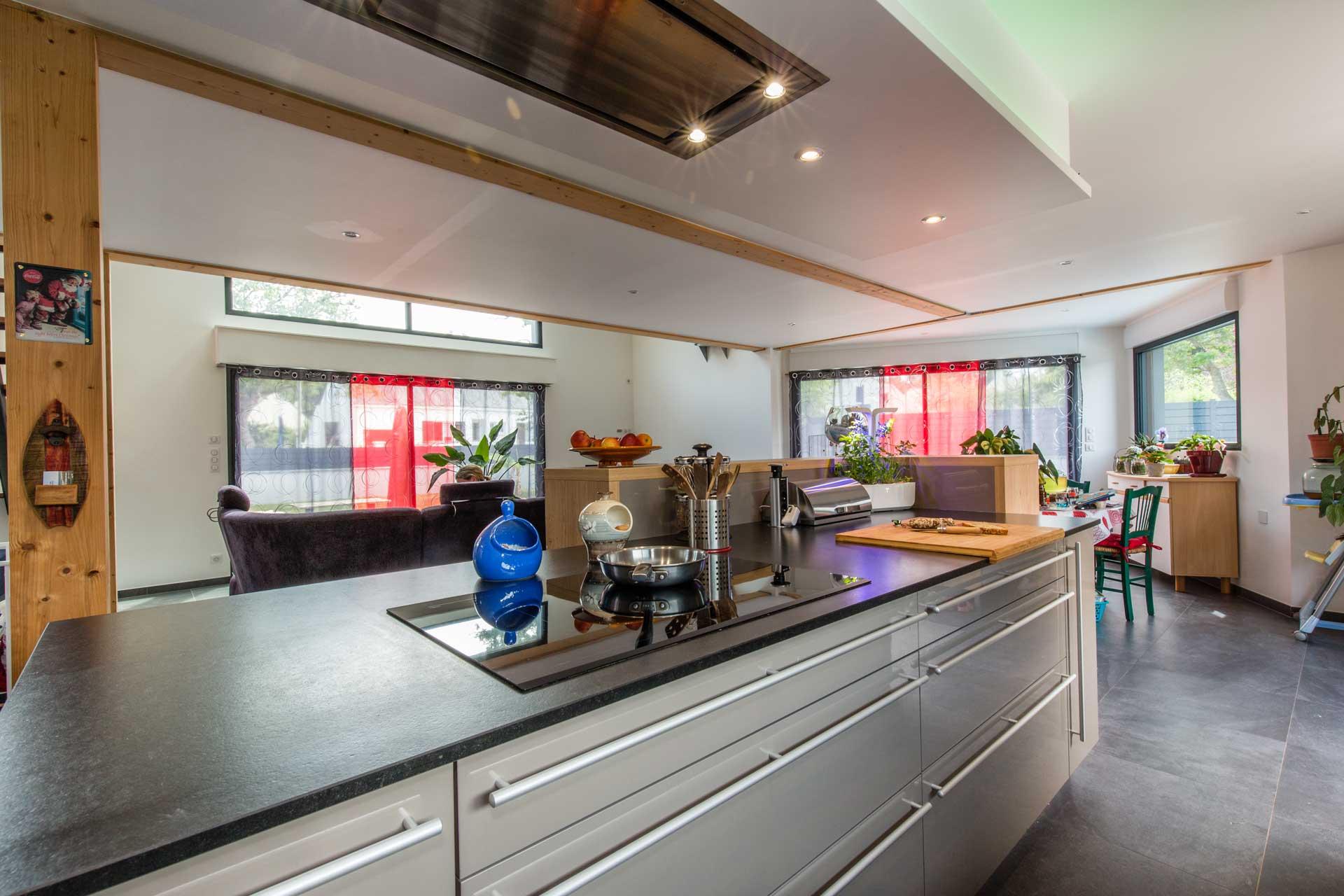 Très contemporaine cette cuisine allie le brillant de la laque des façades avec le bois et le noir structuré du granit
